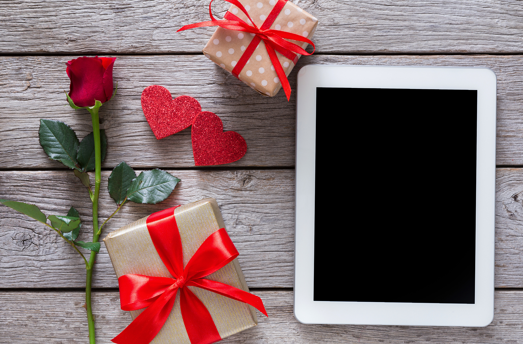 Online shopping holiday background. Tablet screen, rose flower and paper hearts on rustic wood